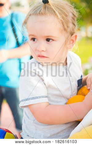 childhood and happiness. healthy food and eating. small baby boy or cute child with adorable face and blonde hair in shirt holds orange fruit sunny summer outdoor on blurred background