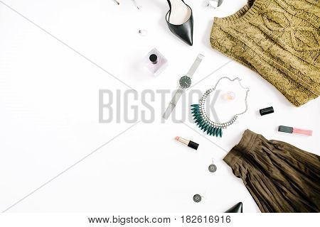 Beauty blog concept. Female clothes and accessories: green skirt and sweater watches necklace lipstick shoes sunglasses on white background. Flat lay top view trendy fashion feminine background.