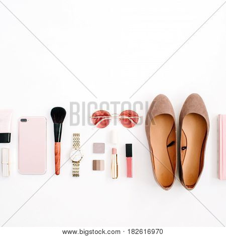 Beauty blog fashion concept. Female pink styled accessories: cell phone watches sunglasses notebook cosmetics shoes on white background. Flat lay top view trendy feminine background.