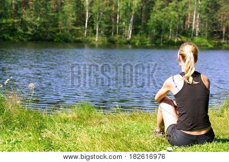A girl sits on the shore of a lake in summer and admires nature.
