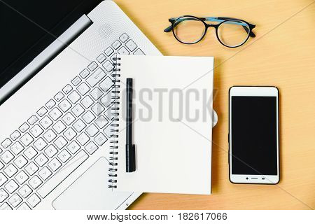 computer notebook with smartphone notebook message and a pen on working desk in office background