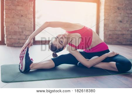 Young Fit Sportswoman Stretching On The Mat On The Floor. She Is Relly Bendy And Flexible As A Resul