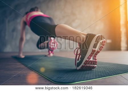 Close Up Of Sportswoman`s Sneakers. She Is Training In Sunny Room On The Mat, Weraing Modern Sportsw