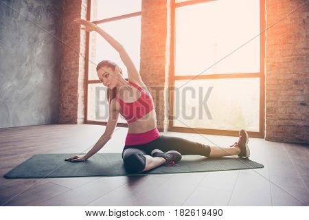 Young Sportwoman Is Making Stretching On Green Mat On The Floor Of Sunny Room. She Is Focused And Se