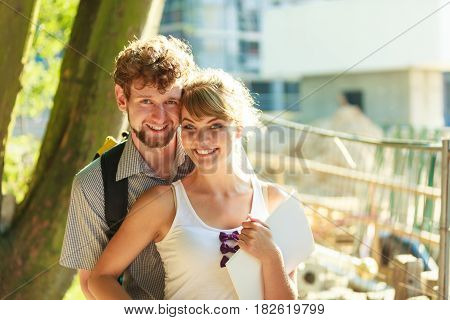 Real estate and family concept - young couple looking at blueprint project building plans dreaming about new house in modern residential area construction site in the background