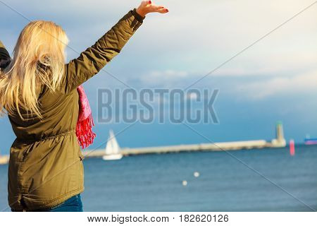 Leisure spending free time outside healthy walks concept. Woman wearing warm jacket having her hands raised up relaxing on beach near sea enjoying beautiful weather cold sunny day