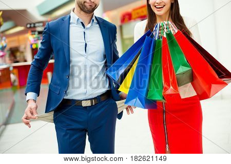It's Shopping And Fun Time! Photo Of Young Cheerful Couple In A Mall, Man Showing His Emrty Pockets,