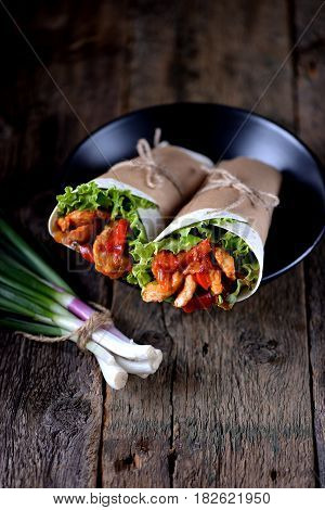 Fajitas with chicken, pepper, onion in a spicy tomato sauce, served in a tortilla.