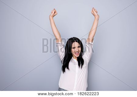 Yeah! Portrait Of Happy Cute Young  Woman With Toothy Smile Raised Hands And Celebrate Victory
