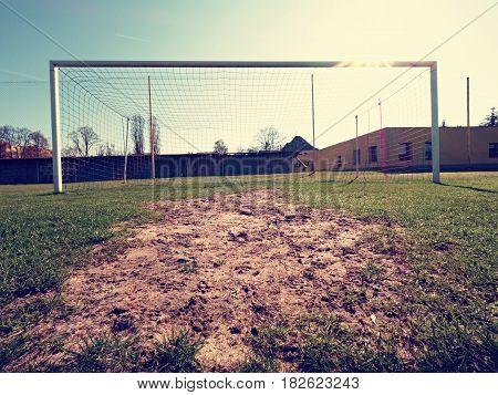 Soccer Football Net Background Over Green Grass And Blurry Stadium.