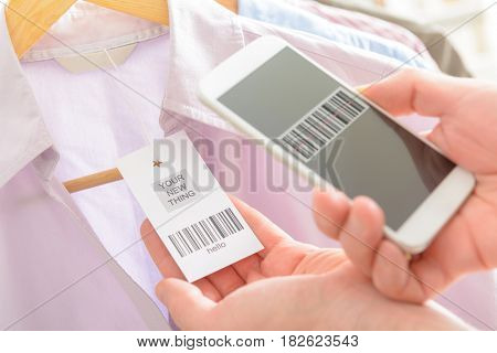 Woman scanning barcode from a label in a shop with mobile phone