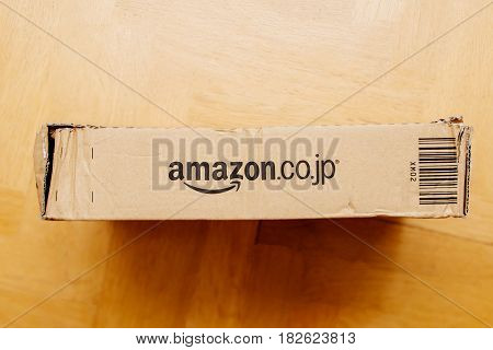 PARIS FRANCE - APR 9 2017: Horizontal view of Amazon Japan (Amazon.co.jp) logotype printed on cardboard box side seen from above on a wooden floor bakground. Amazon Inc is the an American electronic e-commerce company