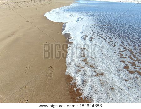 Sea tide with foot prints on a sunny day