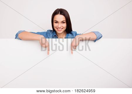 Cheerful Cute Girl Is Standing Behind The White Blank Banner And Pointing Down At A Copyspace