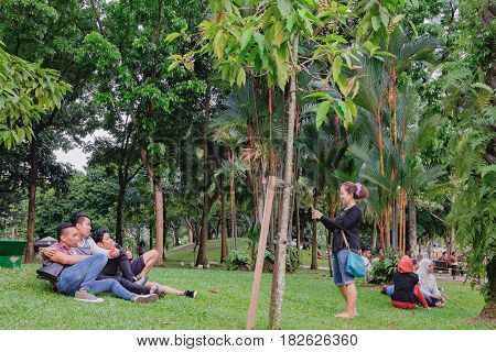 Kuala Lumpur, Malaysia - February 10, 2016: Young smiling girl taking photo of their friends on smartphon in KLCC Park, Kuala Lumpur, Malaysia. It is a known place for recreation in the capital