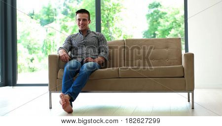 man laying on couch in luxuary villa and using tablet