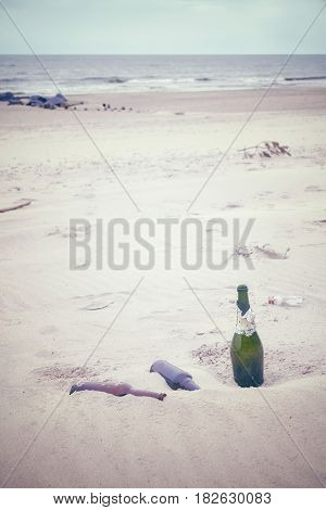 Color Toned Picture Of Empty Liquor Bottles Left On A Beach.