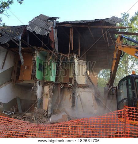 Closeup of Demolition by Backhoe of Old Building. Destroyed house