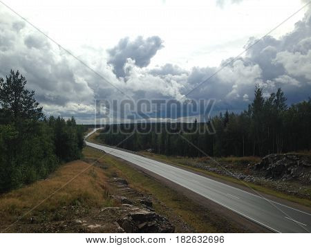 Long way road. Distance, asphalt, sky. Let's hit the road! A road disappears in to the the wide open blue sky, highway, road through colorful forest