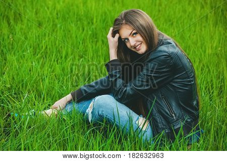 Attractive young blonde girl in a gray coat and jeans sitting on grass and smile in nature.