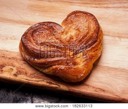 Yeast sweet buns in the shape of a heart on a Board on black baking tray. Country house style. Authentically.