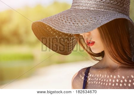 Attractive girl in a black hat worn on the head on the beach. Close up of the face can be seen.