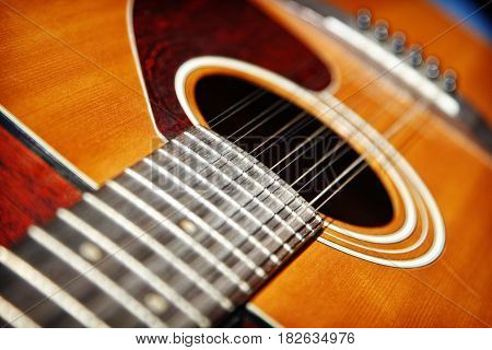 Acoustic Twelve String Guitar.  A close up of the neck and body of an acoustic twelve-string guitar - shallow depth of field.