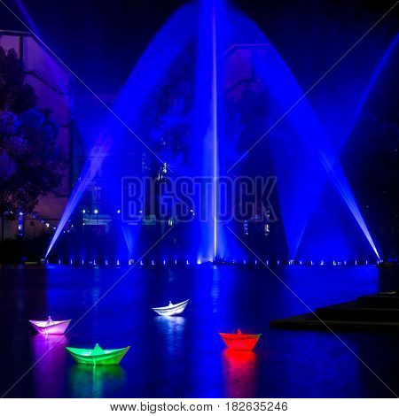BERLIN - OCTOBER 08 2016: Festival of lights. Installation of luminous ships on the water against the background of the illuminated fountain. Potsdamer Platz.