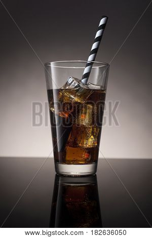 Cola with rum and ice in a glass with a striped straw on a gradient background.