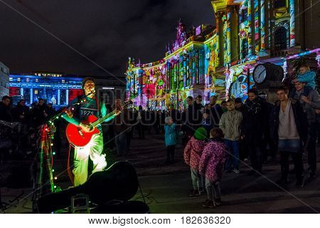 BERLIN - OCTOBER 08 2016: Festival of lights. Musician in the background of the building of the Law Faculty of the Humboldt University in festive illumination.