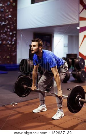 Strong  athlete man in a heavy overhead squat lift in a box gym