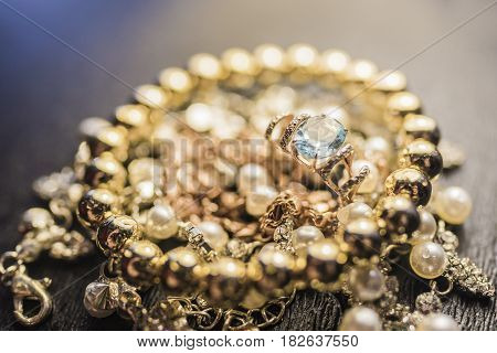 A bright gold ring with a large blue gem and a shiny gold bracelet lie on a necklace with pearls on a dark background. Luxury jewelry concept.