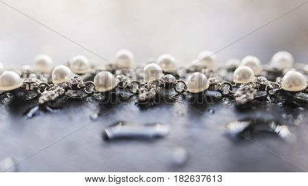 A bright necklace of silver with pearls and shining diamonds lies on a gray background with a drop of water. Luxury jewelry concept.