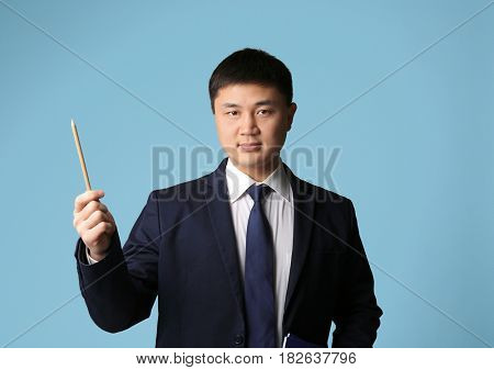 Handsome young Asian teacher on light background