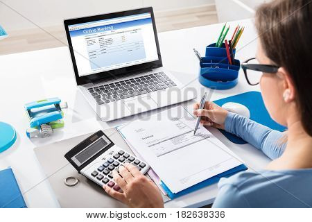 Close-up Of A Businesswoman Calculating Invoice Using Calculator With Online Banking On Laptop Screen