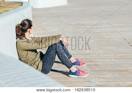 Young Curly Haired Brunette Woman In Sportswear Sitting Outdoors And Resting After Sports Exercises