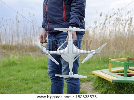 A Man With A Quadrocopter In His Hands. A White Drone Is Being Prepared For The Flight. Phantom.