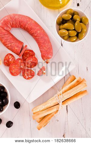 Grissini breadsticks with salami and olives on wooden table.