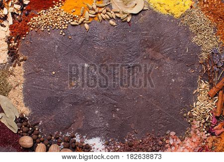 Flat lay composition frame of various spices  over brown slate background, top view