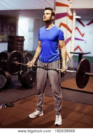 Strong  athlete man in a heavy overhead squat lift in a t box gym