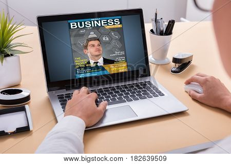 Businessperson Looking At Business Magazine On Laptop At Office Desk