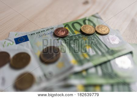 A few euro coins lie on paper money bills of one hundred euros on a wooden table. Financial stability concept.