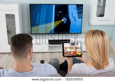 Man Watching The Television With Her Wife Learning Recipe On Tablet At Home