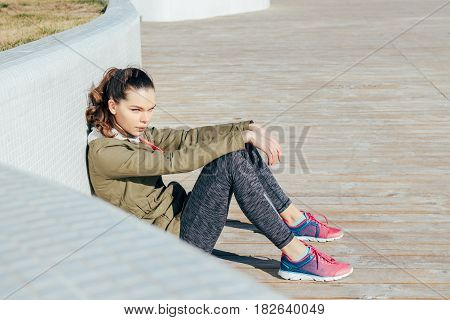 Young Attractive Woman In Sportswear Sitting Outdoors And Resting After Sports Exercises