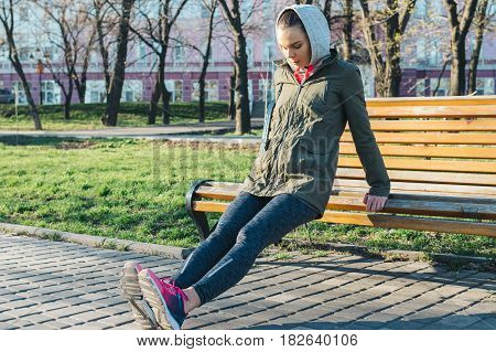 Young Attractive Woman Doing Triceps Exercises In A Park On A Bench