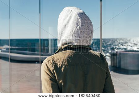 Young Woman In Sports Clothes And A Hood Walking On The Promenade Along The Glass Wall