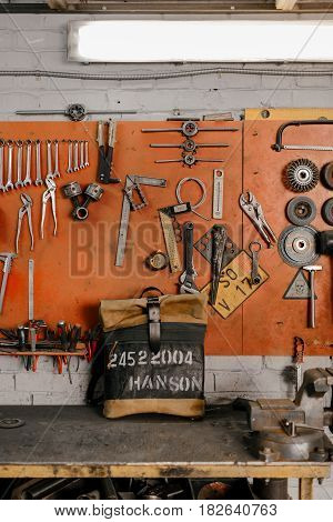 Exclusive leather backpack. Backpack near the wall. The tools in the garage. Many different tools