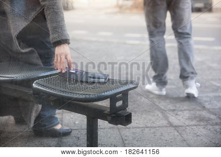 Close-up Of A Woman Picking Up A Lost Wallet On Bench