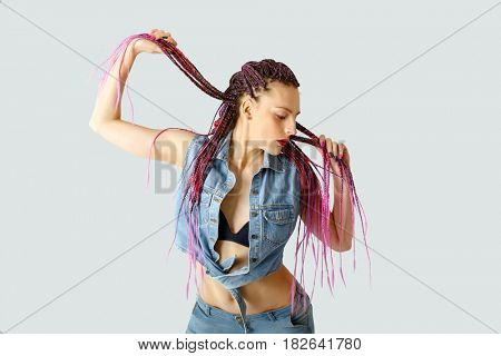 Young beautiful girl with a creative hairstyle. Multiple colored pigtails.