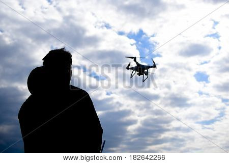 Krasnodar Russia - May 15 2017: A man with a remote control in his hands. Controlling the flight of the drone against the sky. Phantom